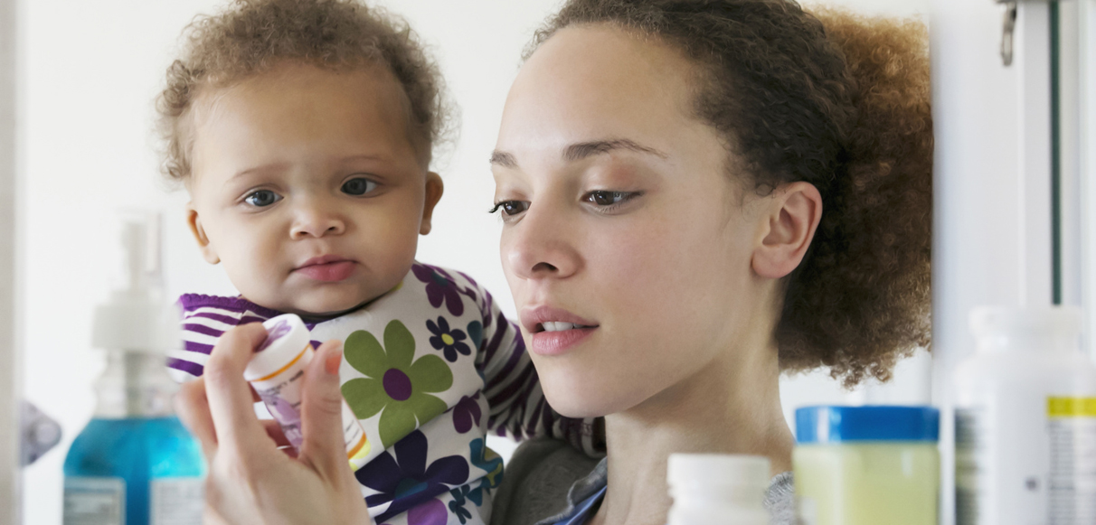 Black mother with baby reading pill bottle